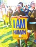 "A young Black man stands in a crowd on a lawn holding a sign that says ""I AM Human"""