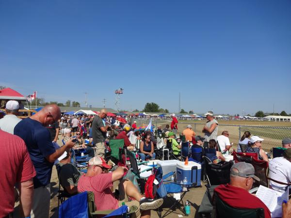 Attendees sit in portable chairs along the top of the track near the backstretch, some consulting race program booklets