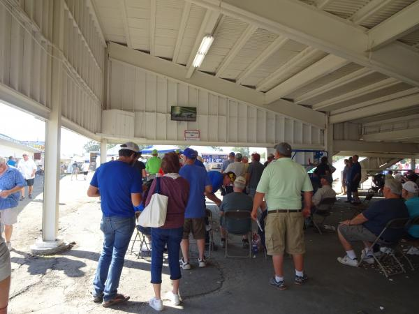 Attendees watch the races below the Grandstand on a mounted television screen.