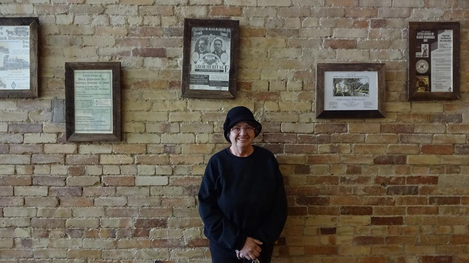 Cheryl Blosser pictured in the Tecumseh Theater amongst past Little Cities of Black Diamonds Day posters