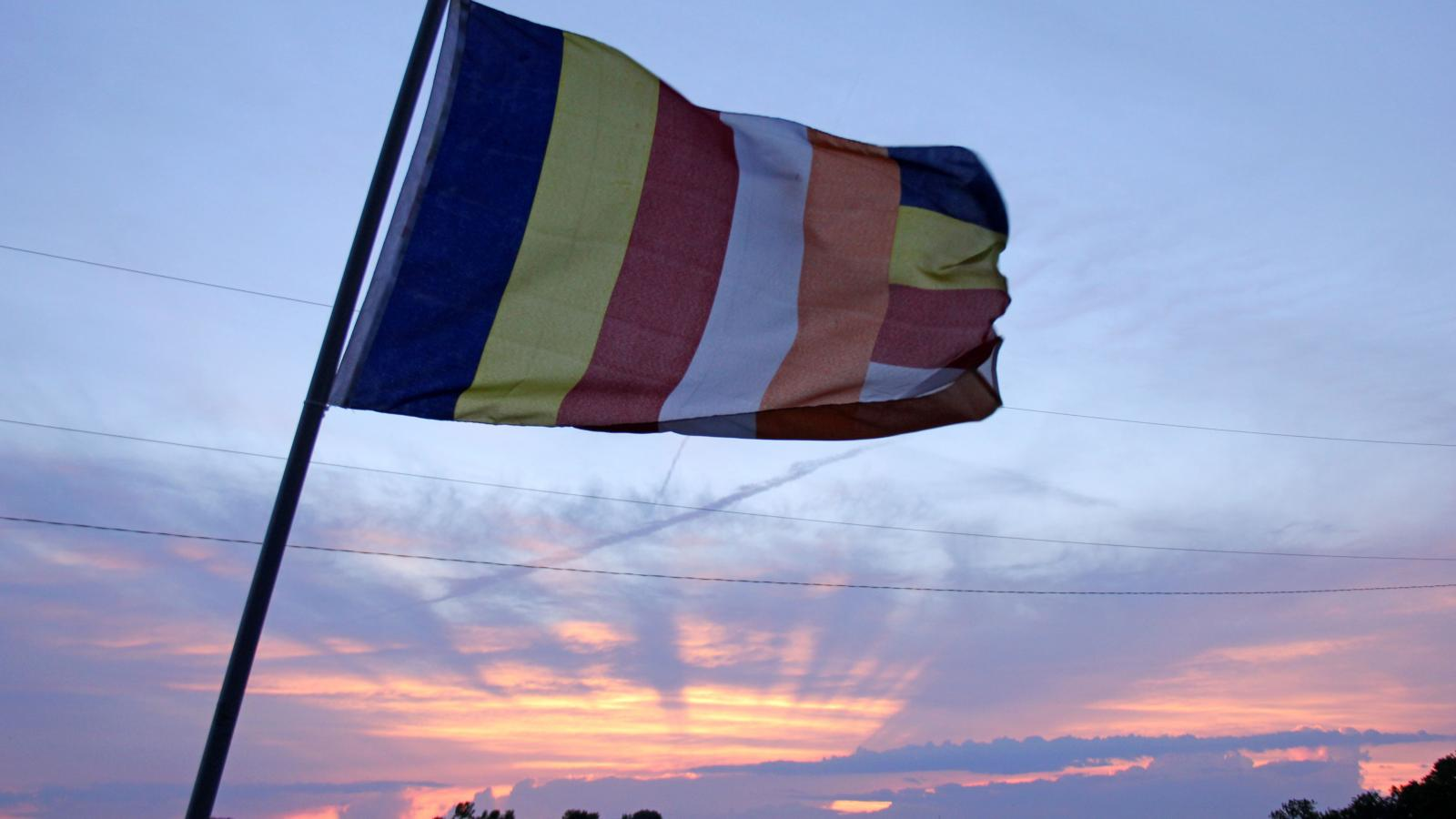The Buddhist flag, created to symbolize and universally represent Buddhism, waves in the wind during sunset outside Wat Buddhasamakidham.