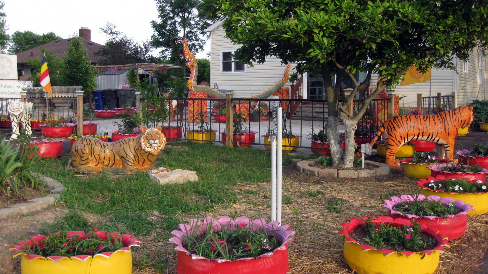 The yard outside the home/temple is elaborately decorated with painted concrete animals and colorful up-cycled tire planters, all of which were created by the various monks that have lived in Wat Buddhasamakidham.
