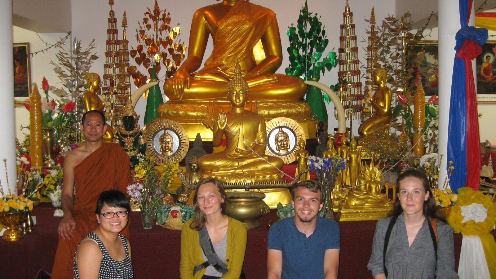 Field research students Dan, Ada, Austin and Kati pictured with Wat Buddhasamakidham Theravada monk Ajanh Sun inside the barn temple.