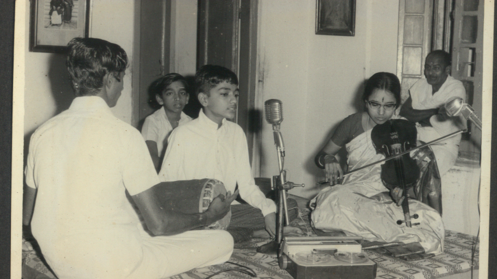 Photo of young Kannikeswaran singing into microphone while others, possibly his family, play instruments