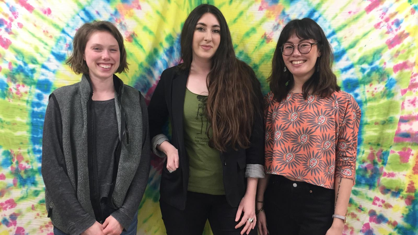Haley (far left), Whitney (center), and Katie (far right) pose in front of a tapestry in a room in the Recovery Council on the group's last day.