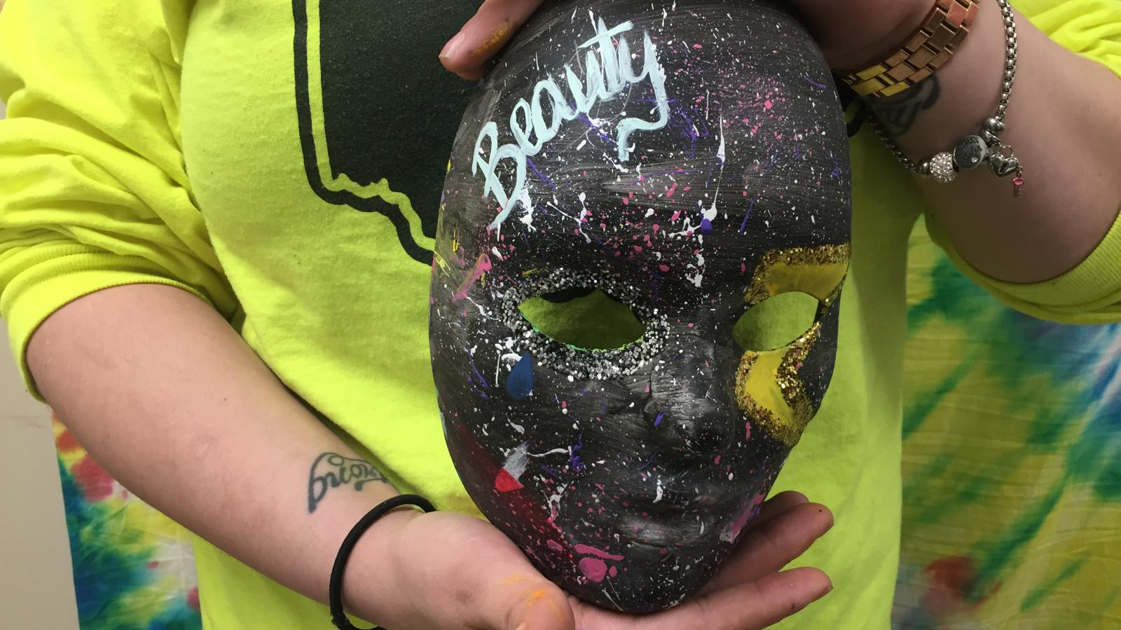 Close-up picture of Liv's art therapy mask as she holds it.