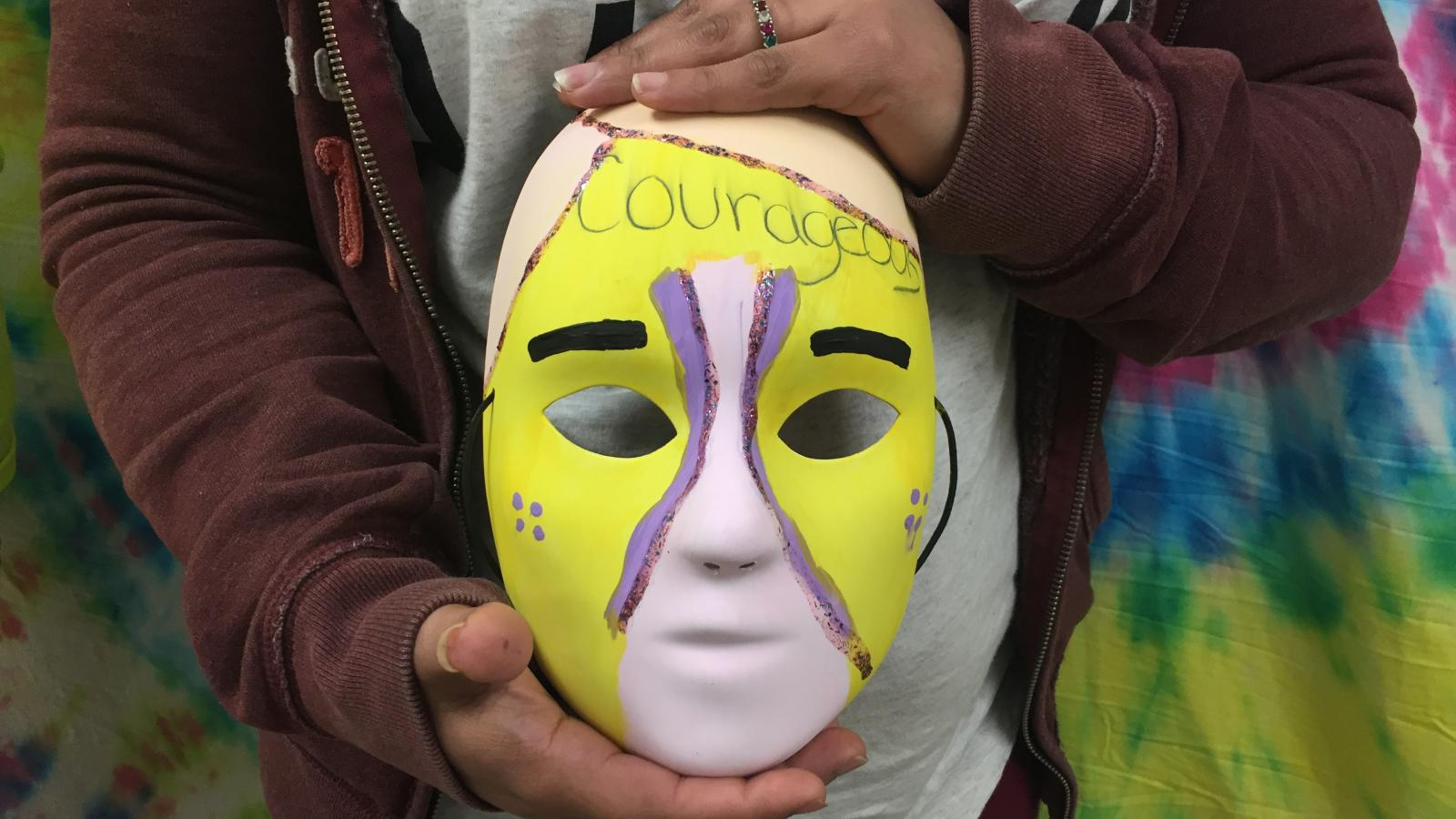 Close-up picture of Kaylena's art therapy mask as she holds it.