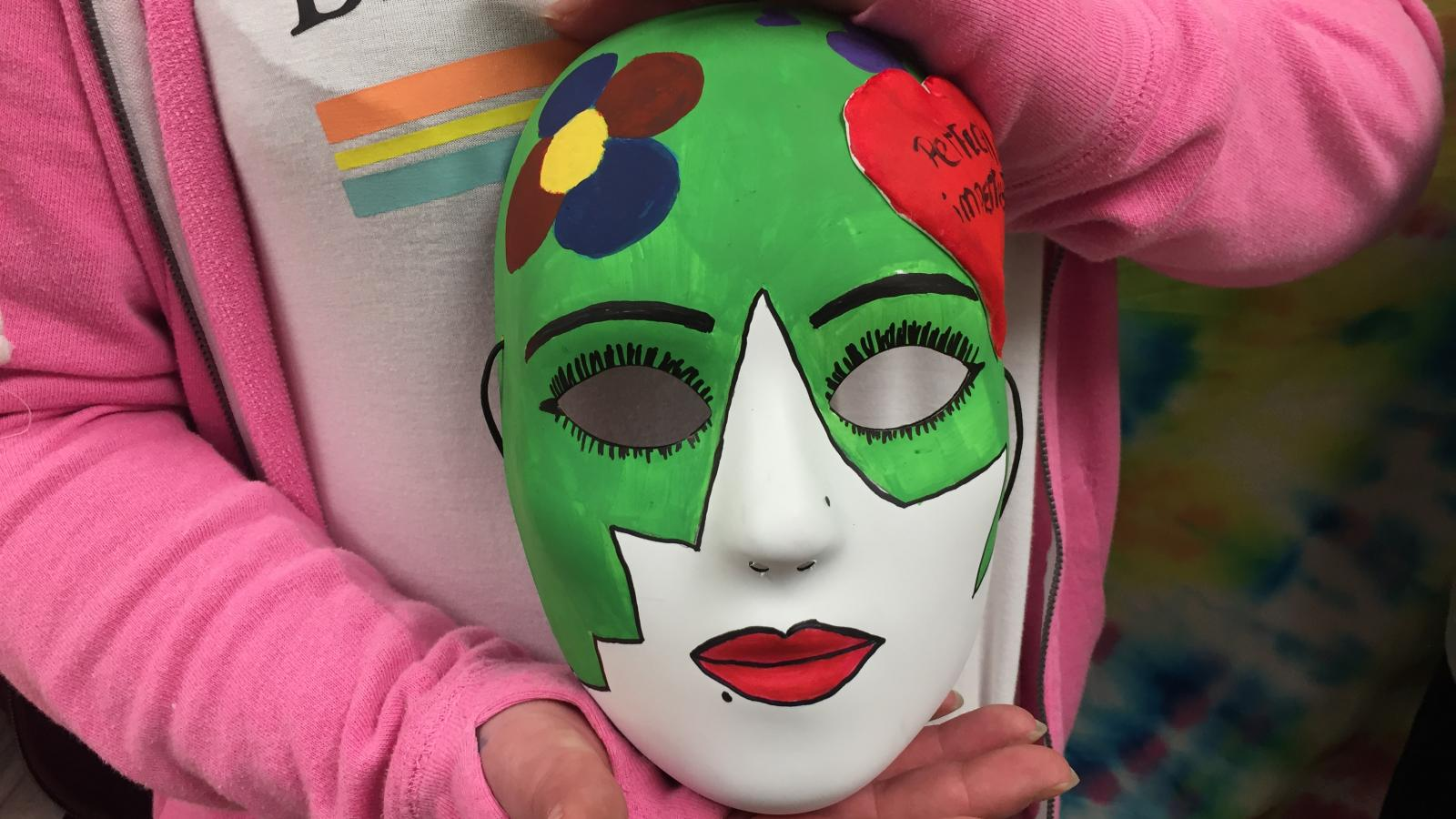 Close-up picture of Fawn's art therapy mask as she holds it.