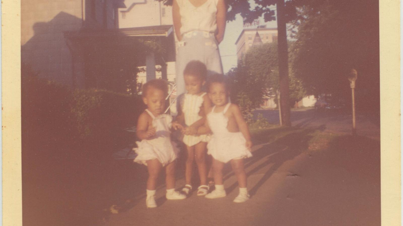 Jennie, Maureen, and Marlene as toddlers with mother Geraldine behind them standing on the sidewalk in front of 709 3rd Street