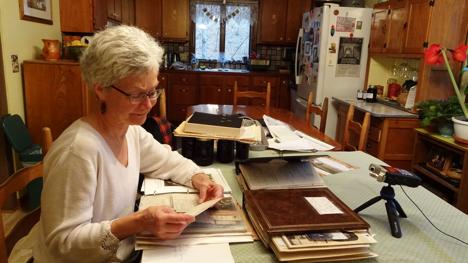 Barb Bradbury sitting amidst documents, photos, and ephemera in her kitchen.