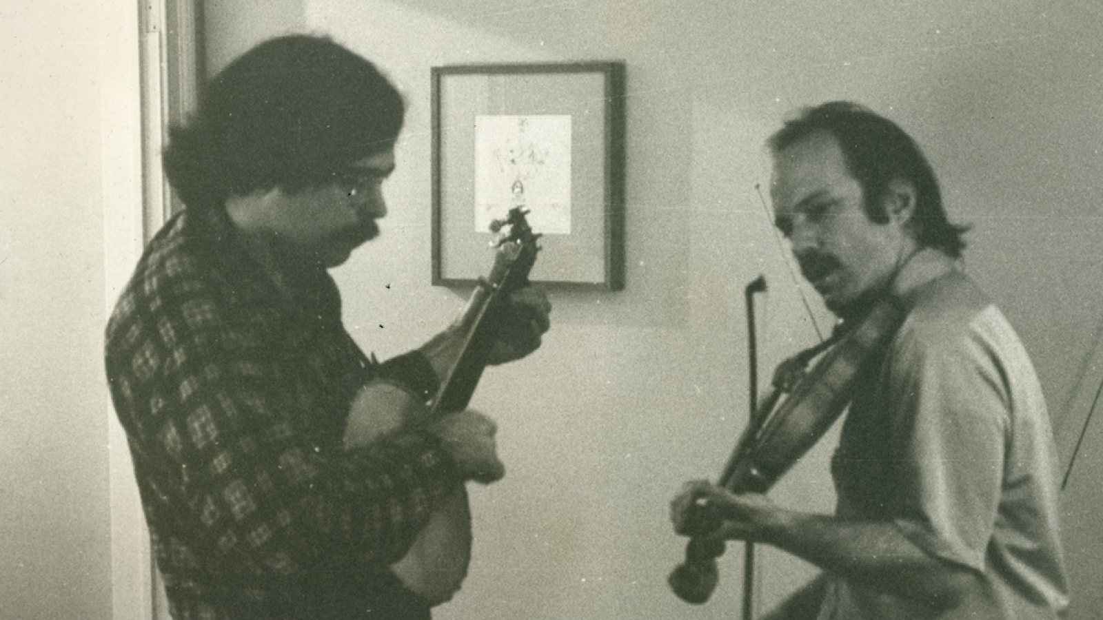 Unger playing banjo in living room with an unknown man, 1973