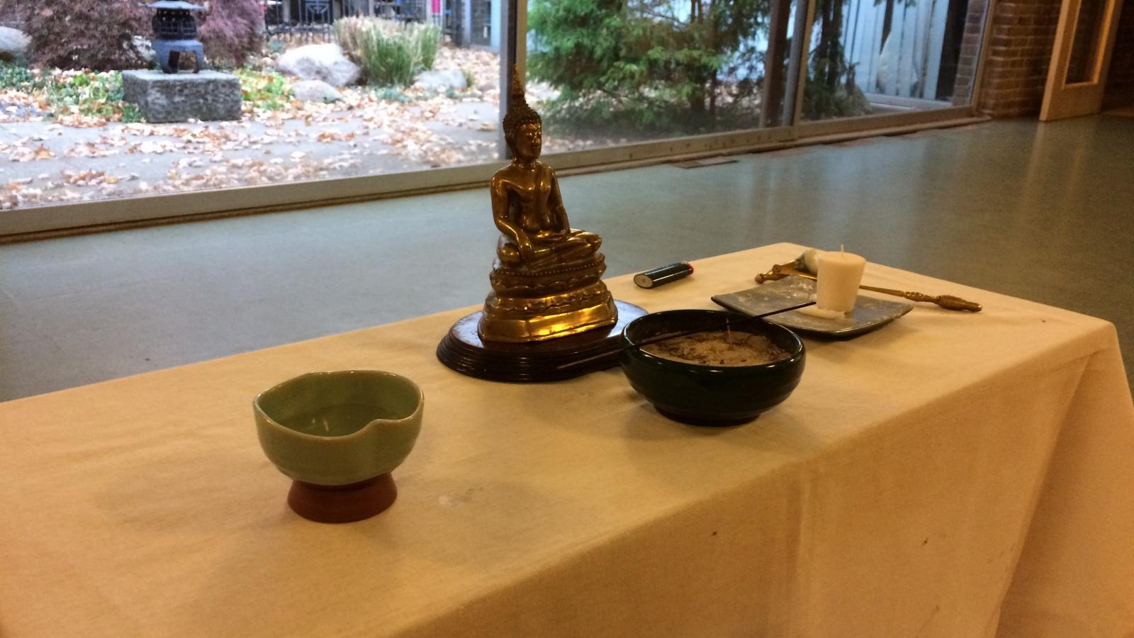 The Buddha altar with a statue of Buddha, incense, a candle and water