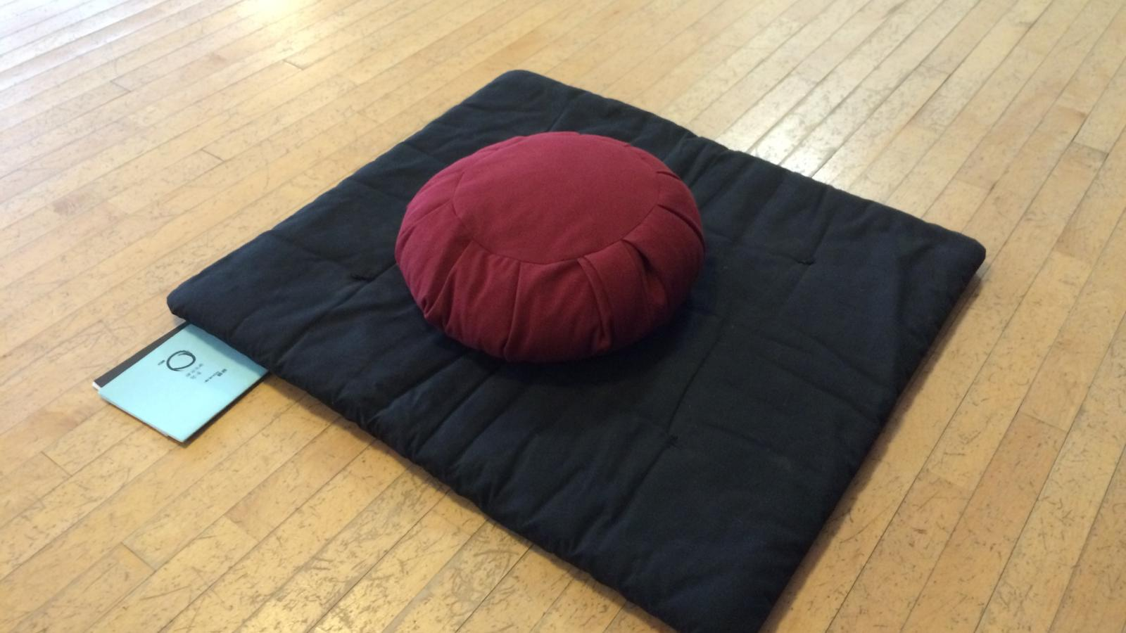A typical meditation zabuton (mat) with a zafu (cushion), along with the sutra books
