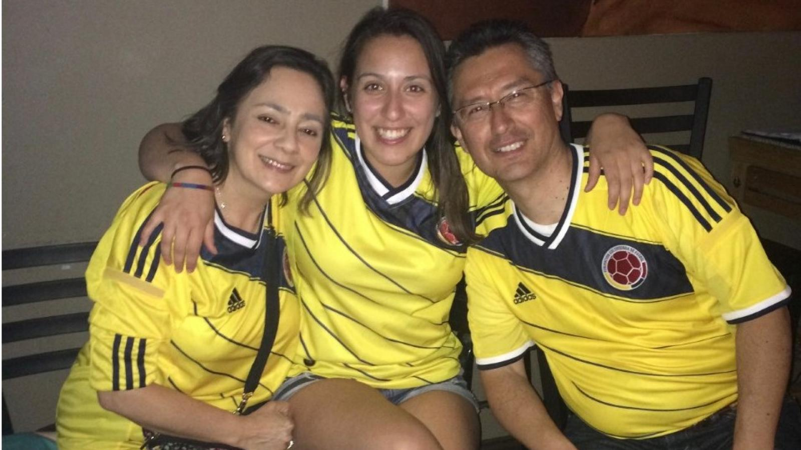 Laura and her parents wearing Colombian jerseys